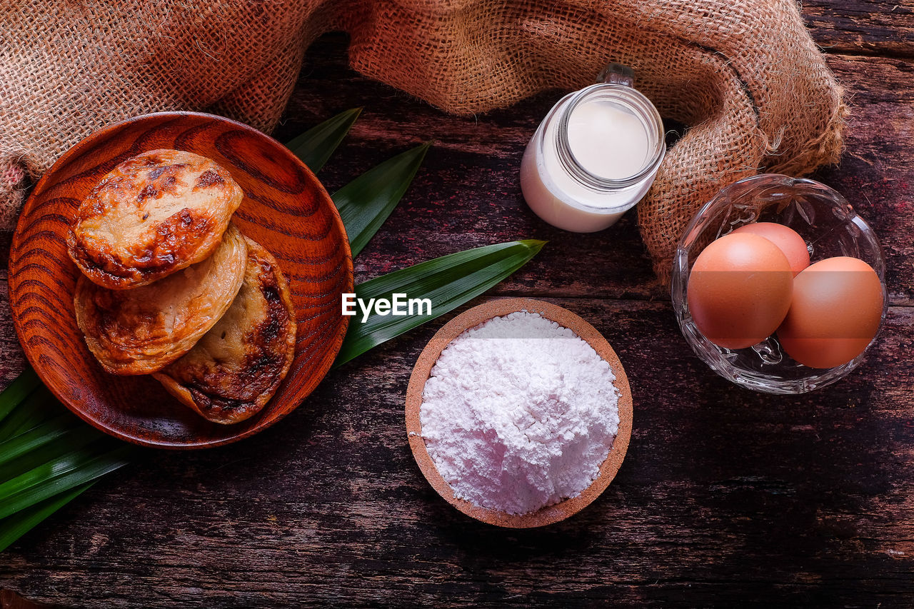 food, food and drink, table, freshness, still life, wellbeing, healthy eating, directly above, indoors, wood - material, no people, bowl, egg, container, brown, high angle view, bread, dairy product, close-up, ingredient, breakfast
