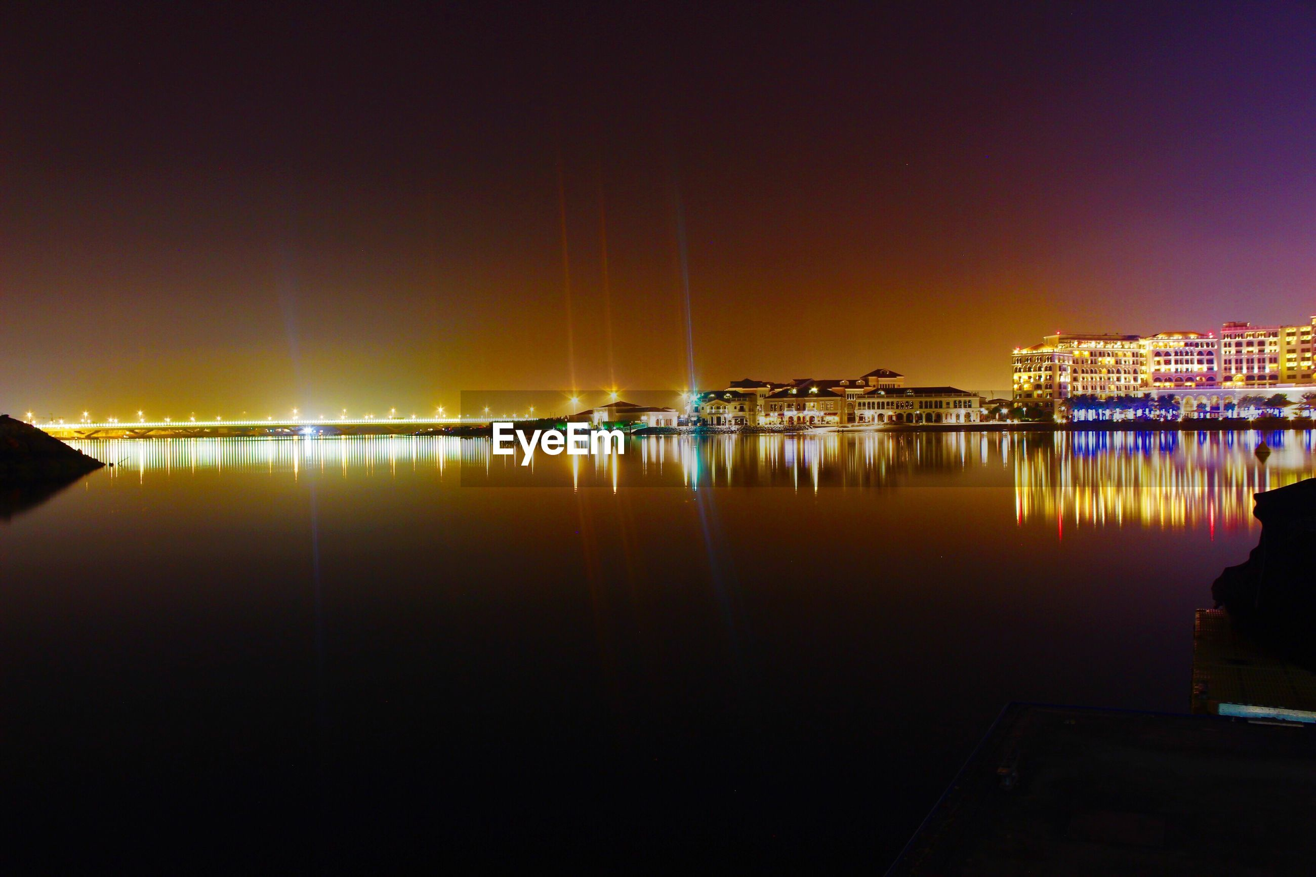Calm lake by illuminated city against sky at night