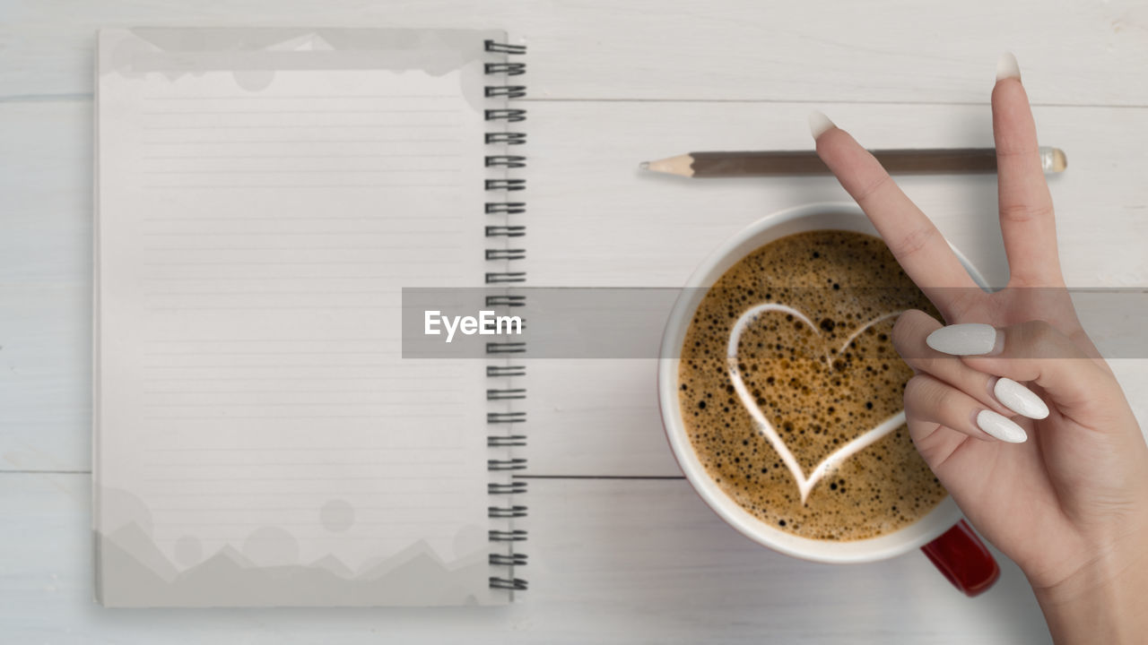 DIRECTLY ABOVE SHOT OF HAND HOLDING COFFEE CUP WITH SPOON