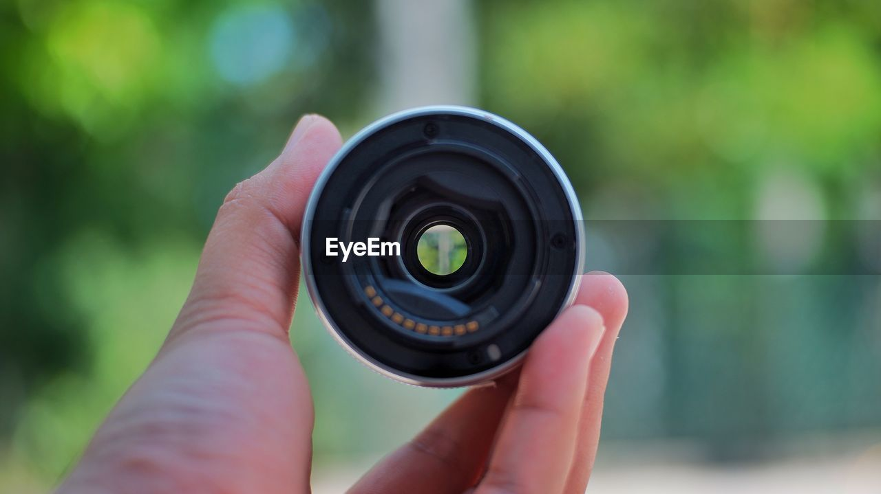 Close-up of hand holding camera lens outdoors