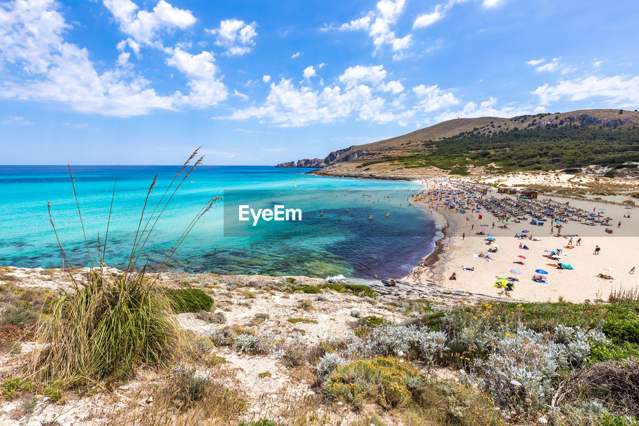 water, sky, cloud - sky, beach, sea, beauty in nature, land, scenics - nature, nature, tranquil scene, tranquility, day, mountain, plant, idyllic, group of people, non-urban scene, horizon over water, horizon, outdoors, turquoise colored