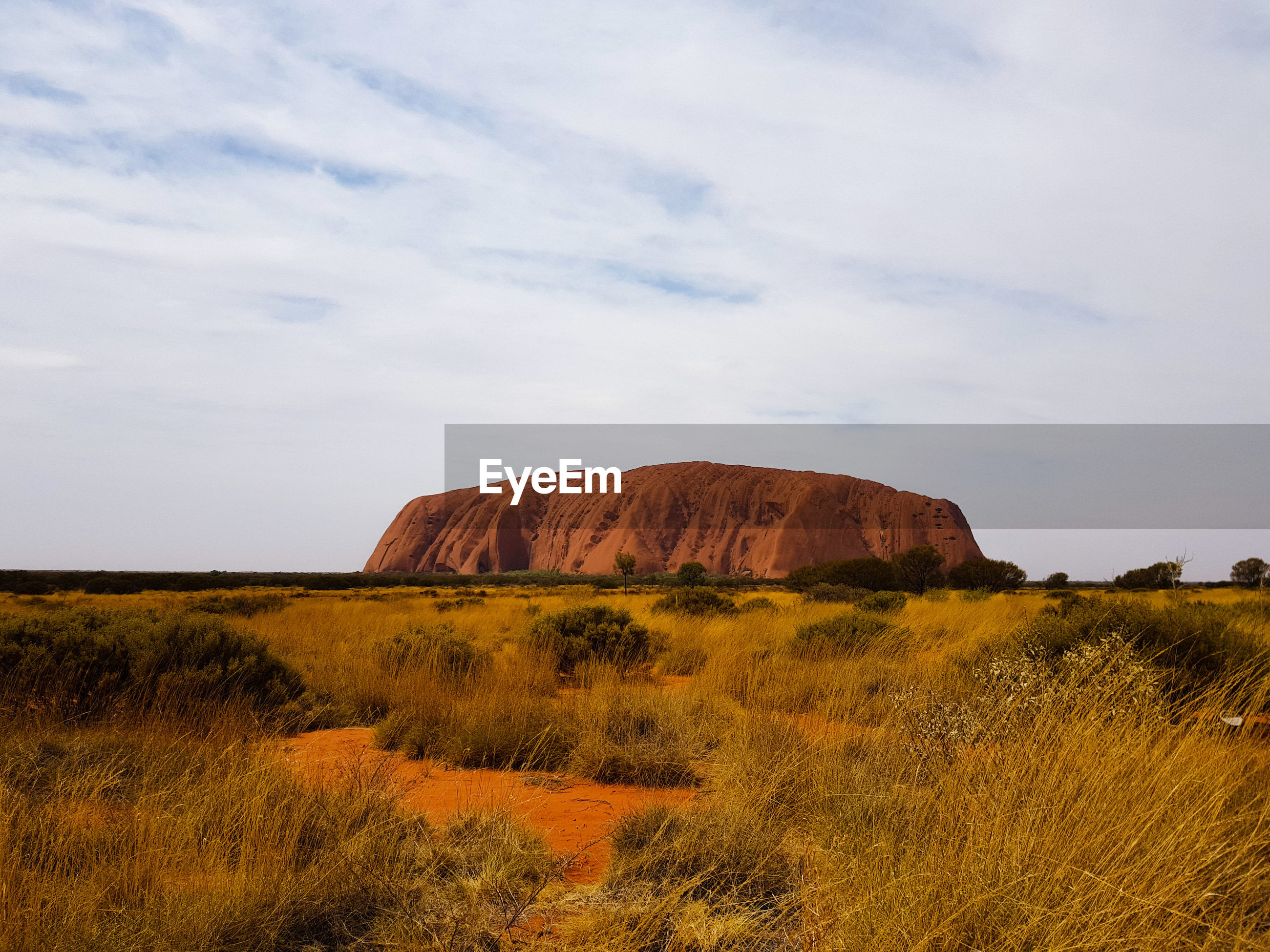 SCENIC VIEW OF ROCK FORMATION ON FIELD AGAINST SKY