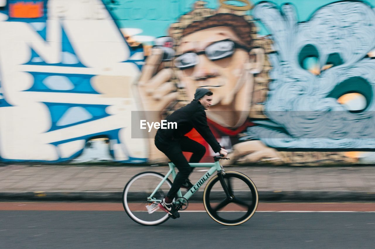 Side view of man riding bicycle on street by graffiti wall