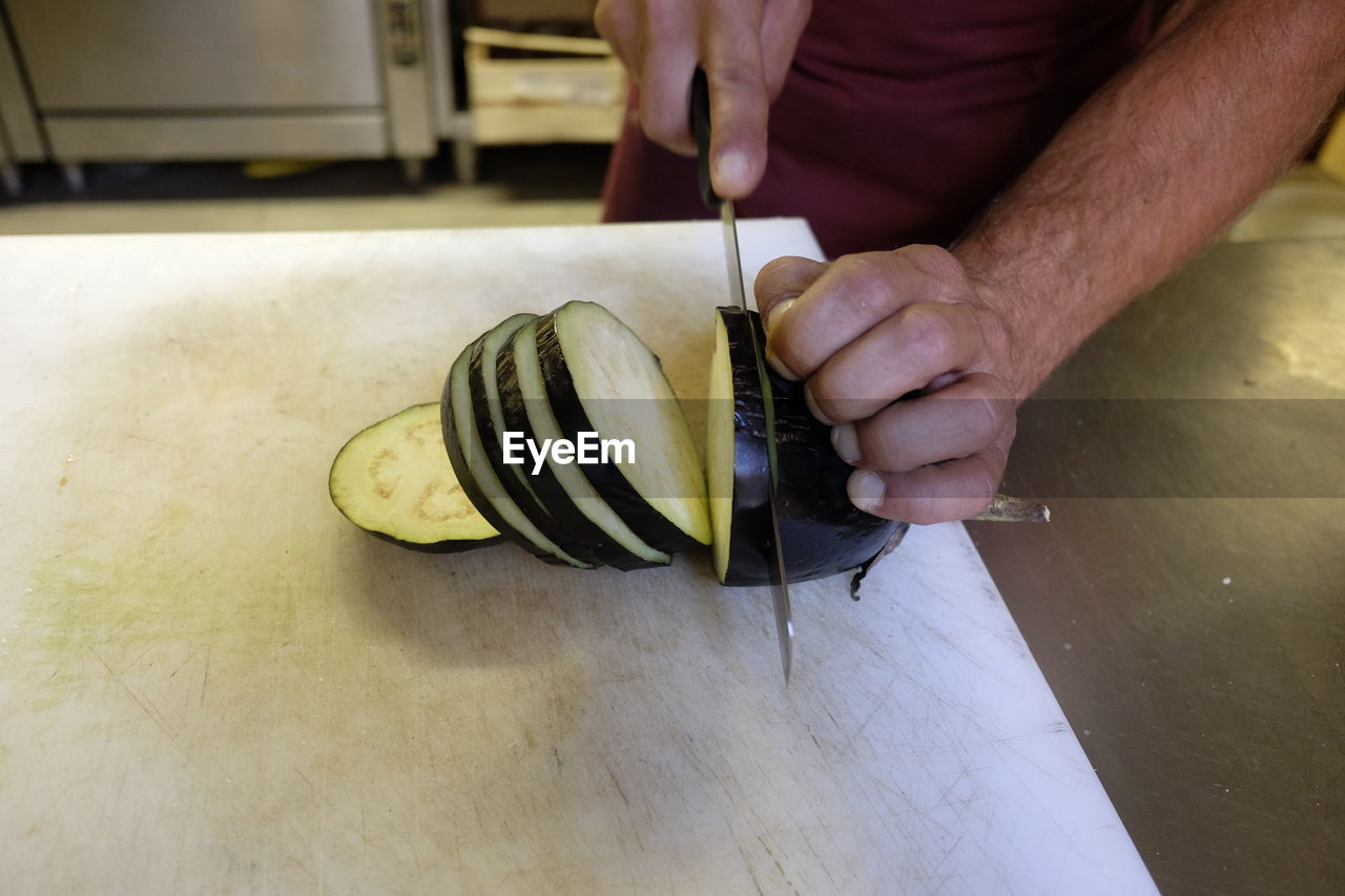 Midsection Of Man Slicing Eggplant On Kitchen Counter