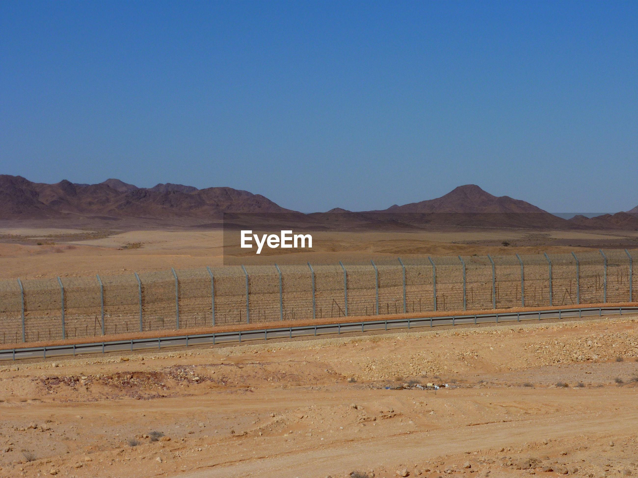 Border in desert against clear sky