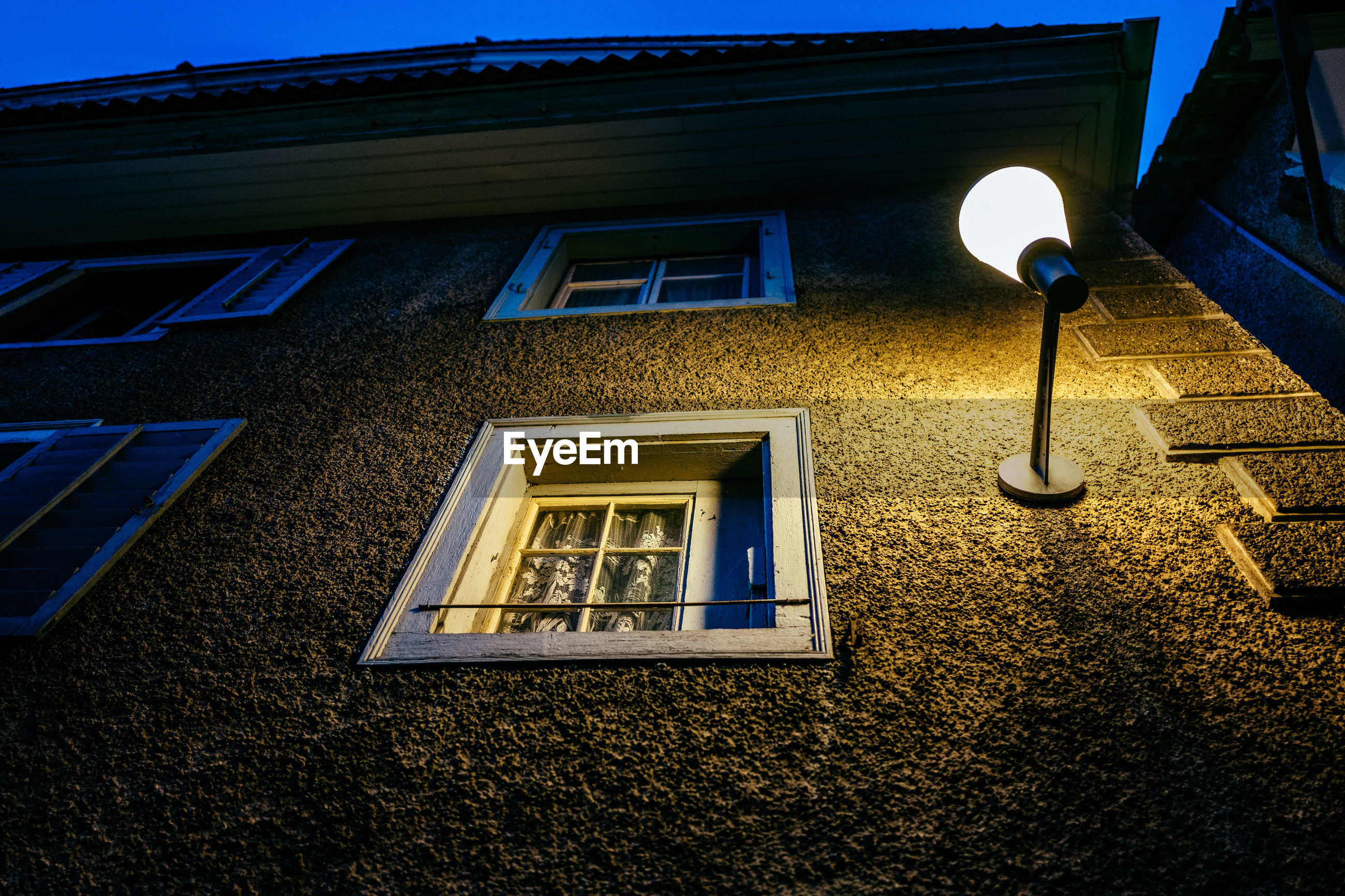 Low angle view of illuminated electric light at building