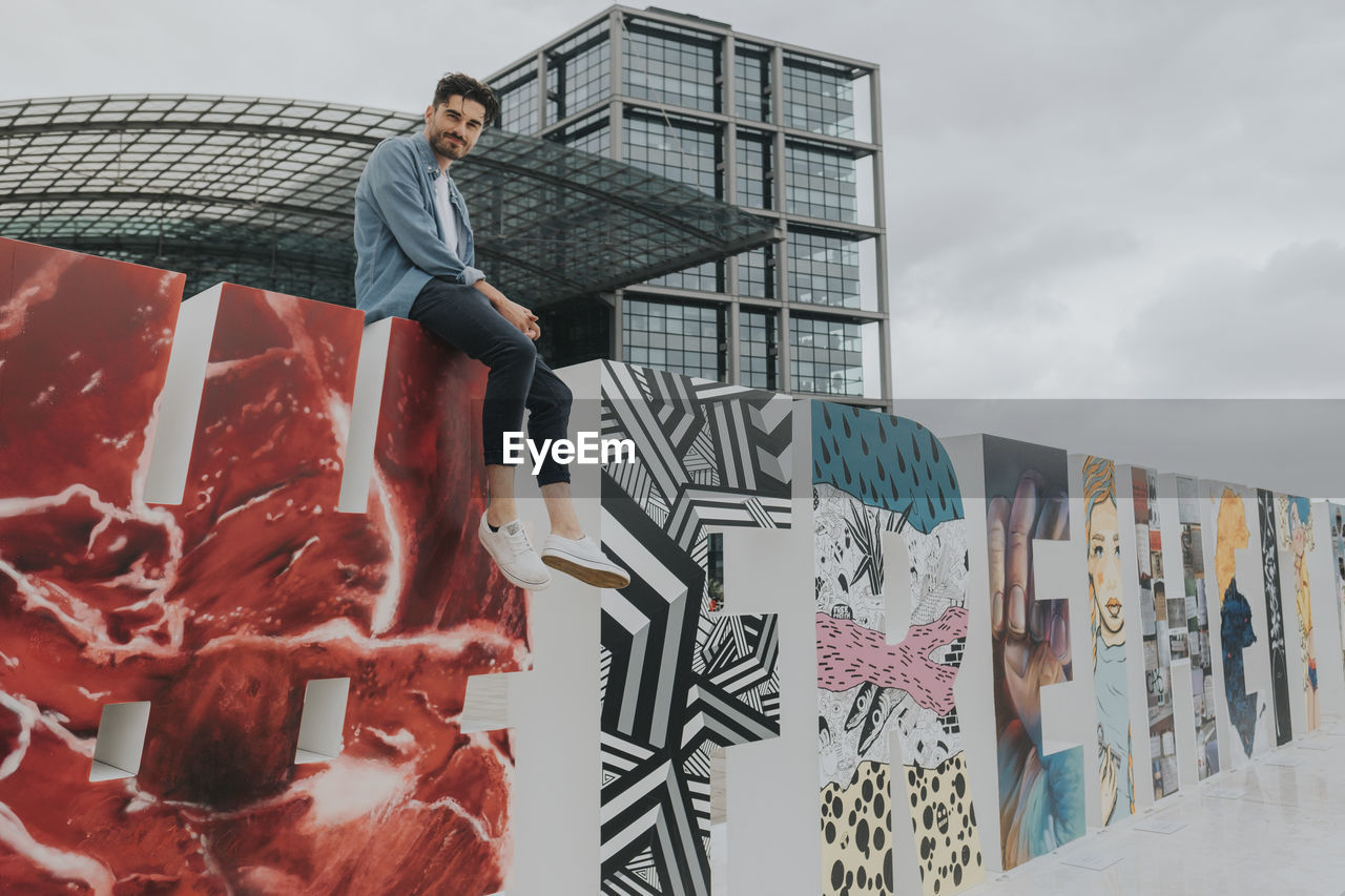 one person, real people, sky, architecture, casual clothing, standing, creativity, built structure, young men, cloud - sky, art and craft, leisure activity, lifestyles, men, young adult, front view, building exterior, day, graffiti, mural