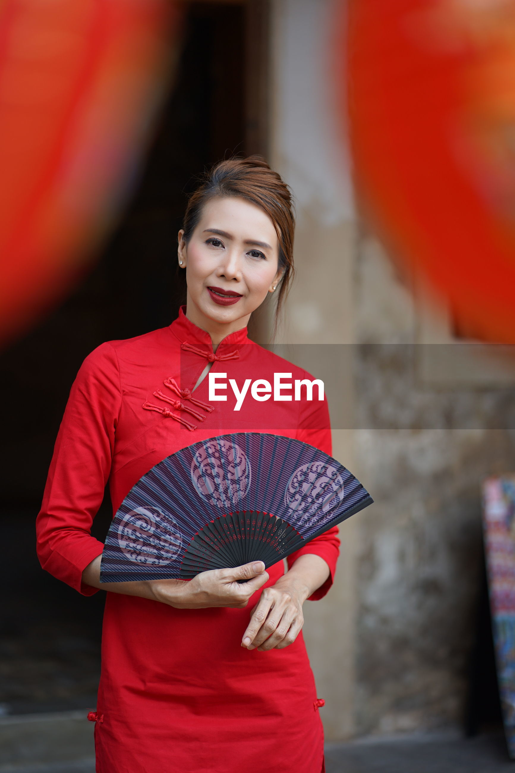 Portrait of smiling woman holding hand fan