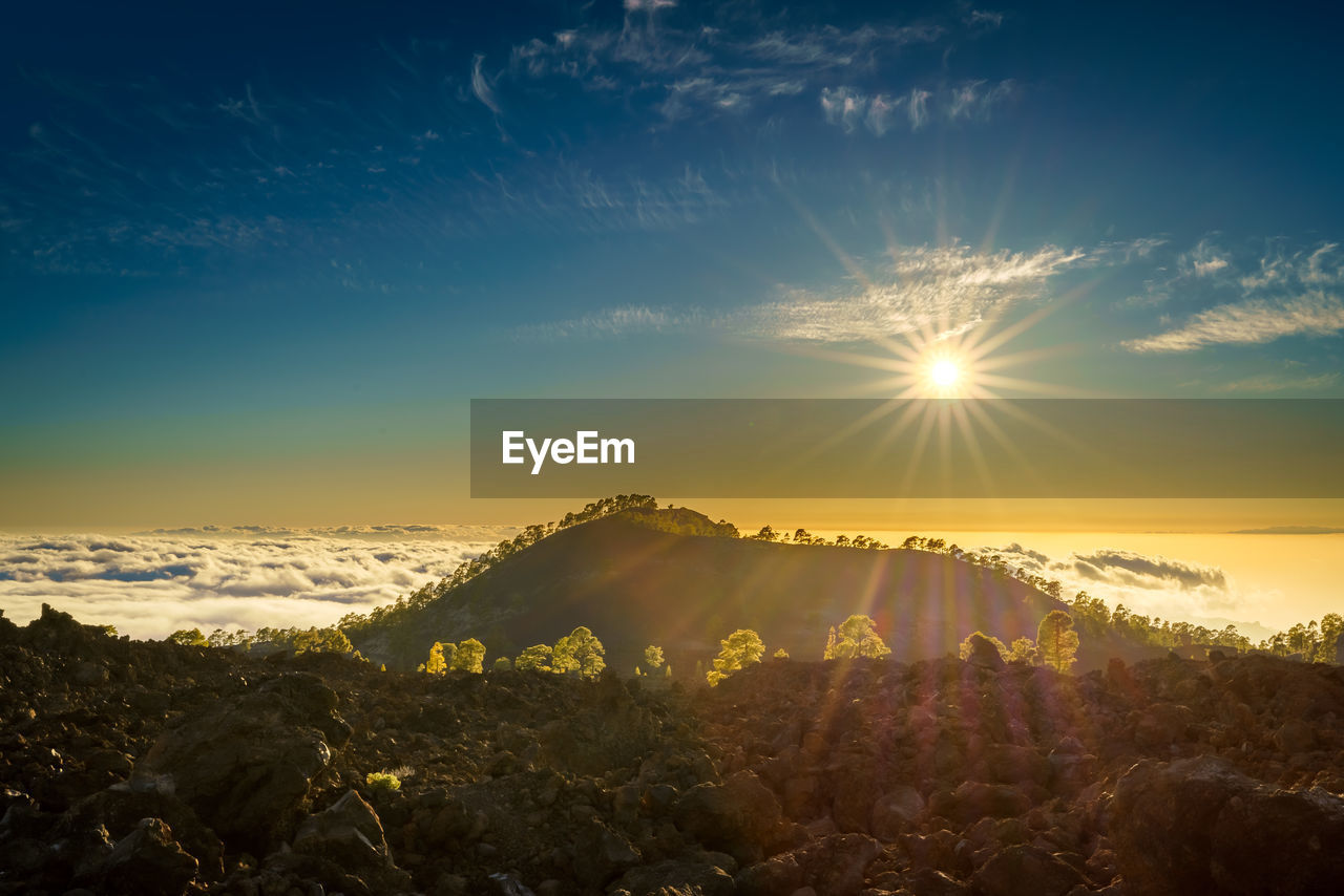 sky, scenics - nature, tranquil scene, tranquility, beauty in nature, sunset, sunlight, cloud - sky, sun, nature, sunbeam, rock, idyllic, no people, lens flare, solid, environment, rock - object, landscape, non-urban scene, outdoors