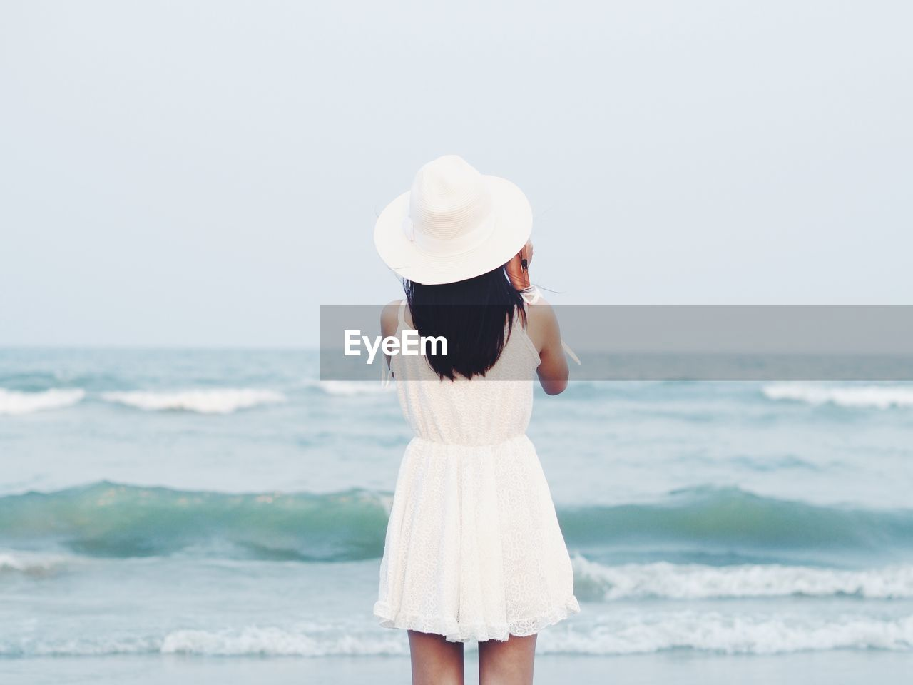 sea, hat, rear view, one person, real people, beach, horizon over water, leisure activity, three quarter length, standing, nature, outdoors, women, sun hat, beauty in nature, clear sky, sky, vacations, water, lifestyles, day, scenics, wave, young adult, adult, people