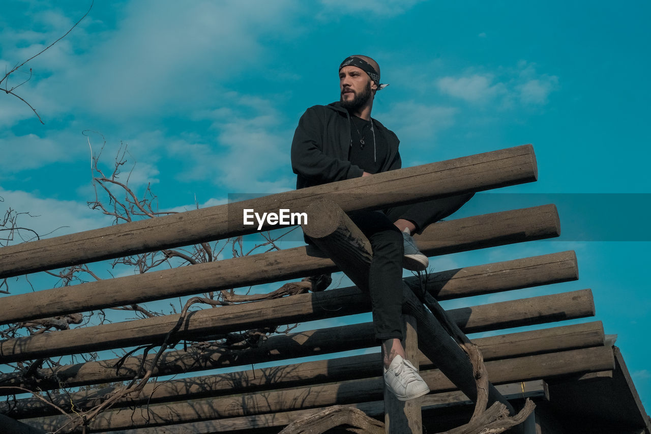 wood - material, sky, low angle view, one person, cloud - sky, casual clothing, young men, real people, young adult, full length, front view, day, sitting, lifestyles, looking away, nature, railing, looking, outdoors
