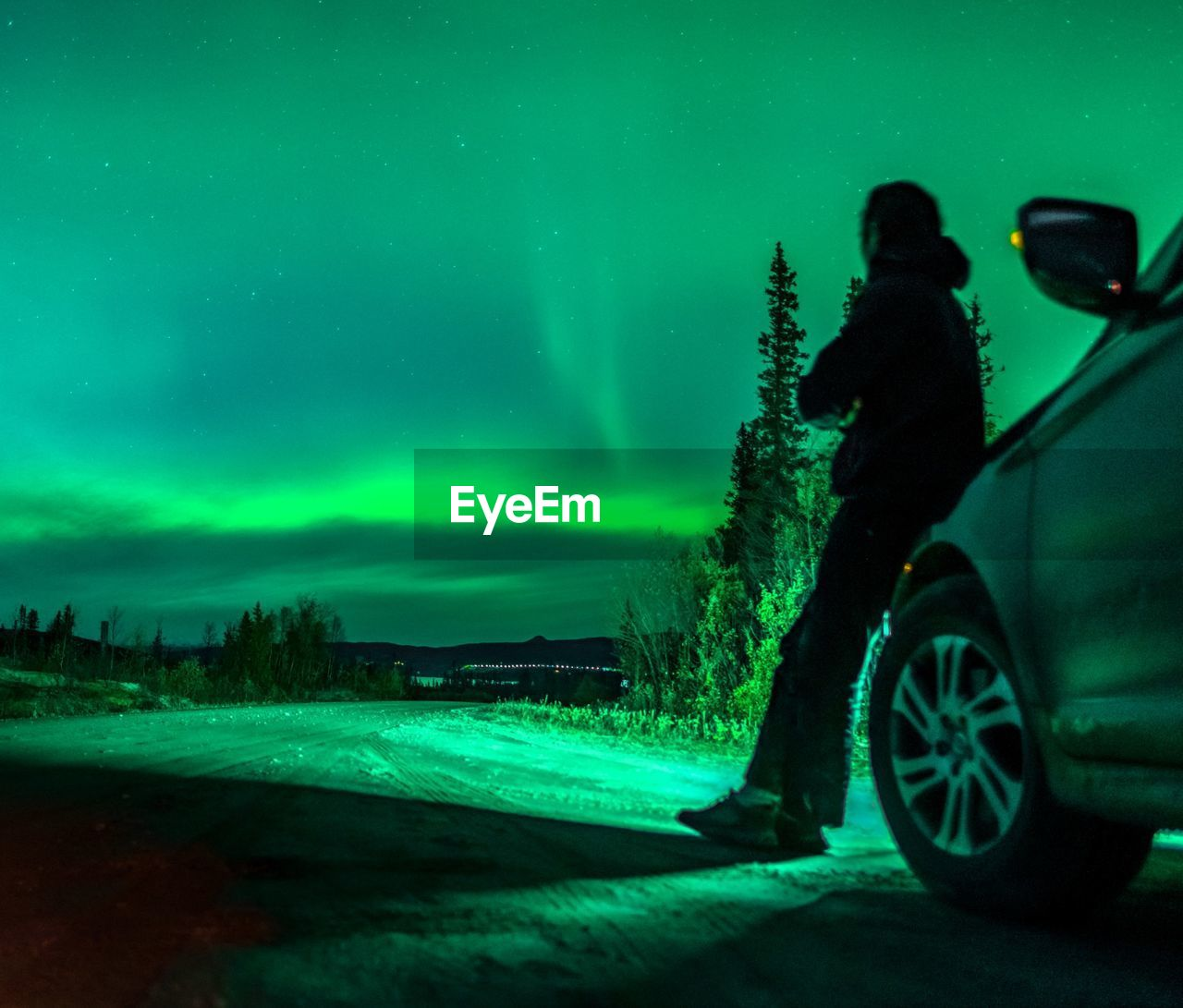 Person Leaning On Car Against Aurora Polaris At Night