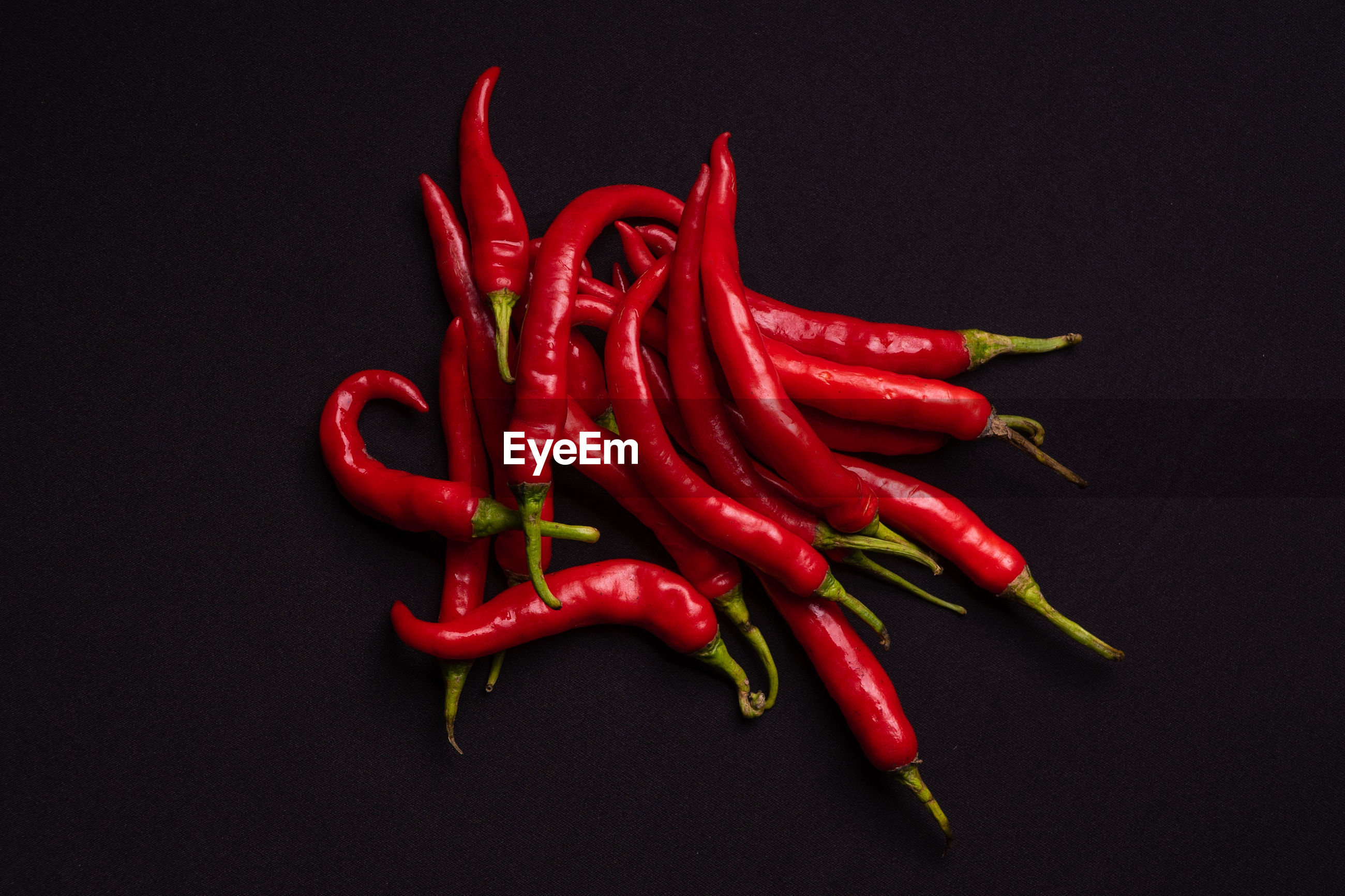 CLOSE-UP OF RED CHILI PEPPERS OVER BLACK BACKGROUND