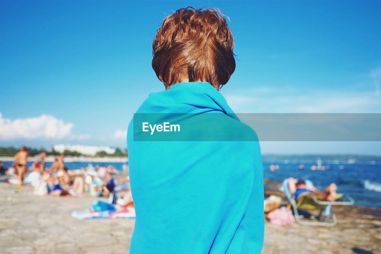 Rear View Of Boy Standing At Beach Against Blue Sky