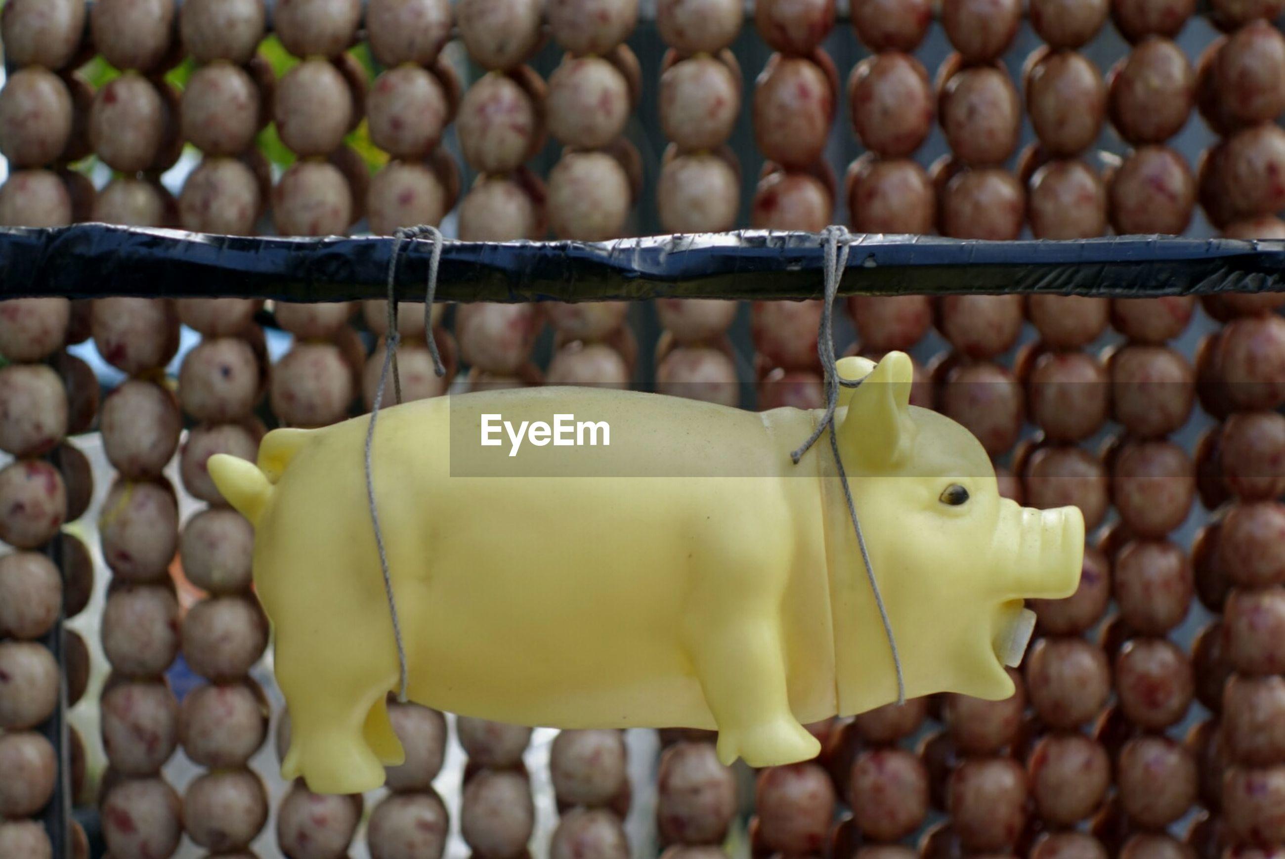 Close-up of toy pig hanging against pork balls at market for sale