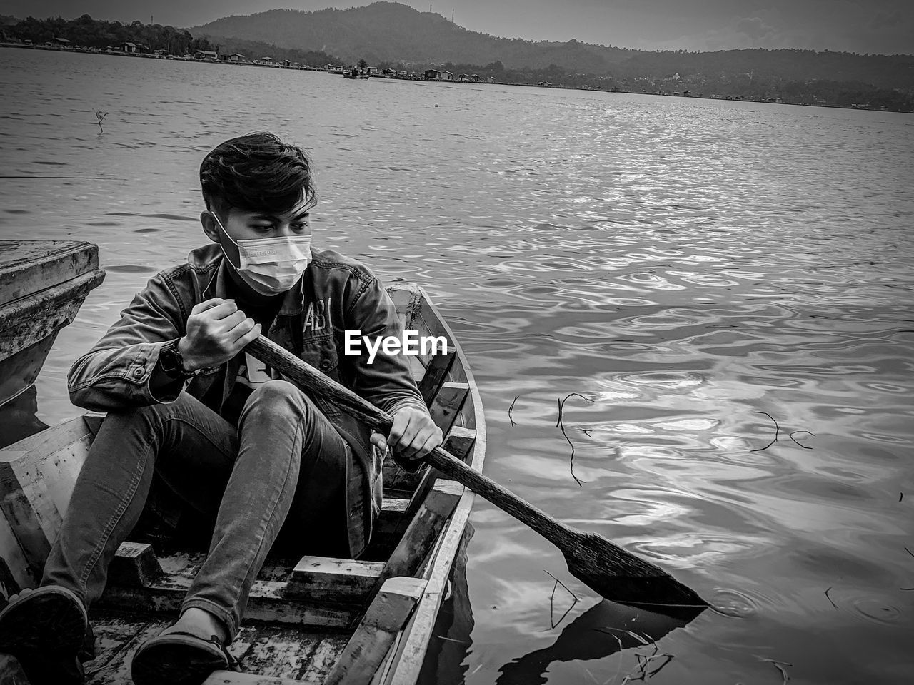 YOUNG MAN SITTING IN BOAT AT LAKE