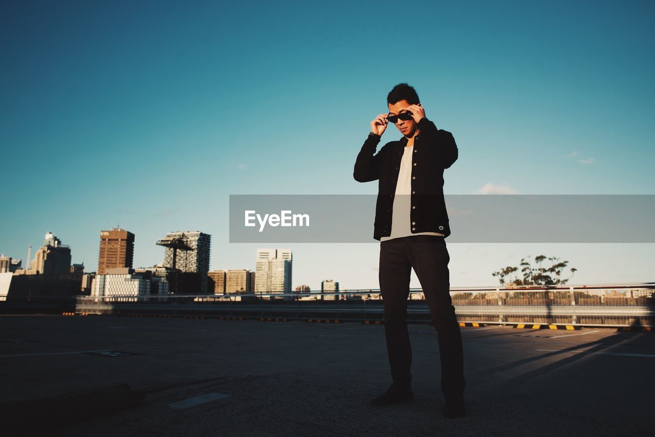 Low Angle View Of Man Wearing Sunglasses Against Clear Sky