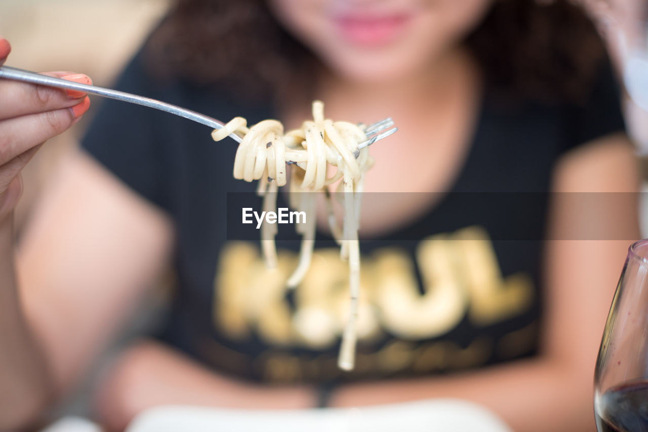 Midsection of woman eating noodles