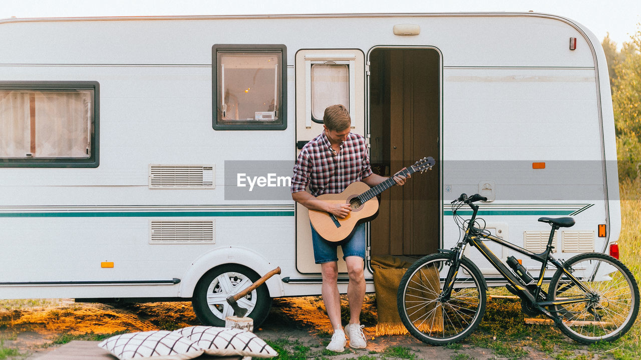 A man with a guitar stands near a trailer at sunset