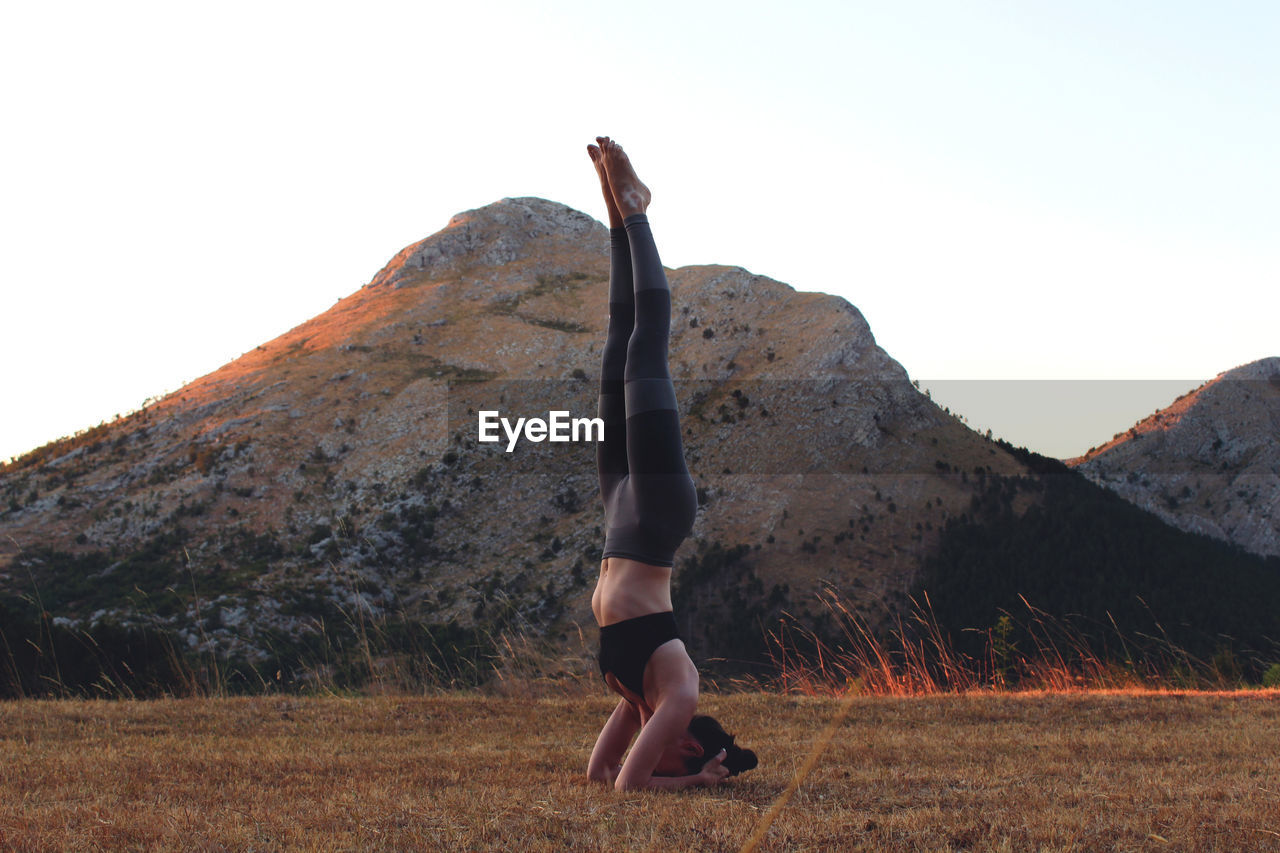 Woman Exercising On Field Against Clear Sky