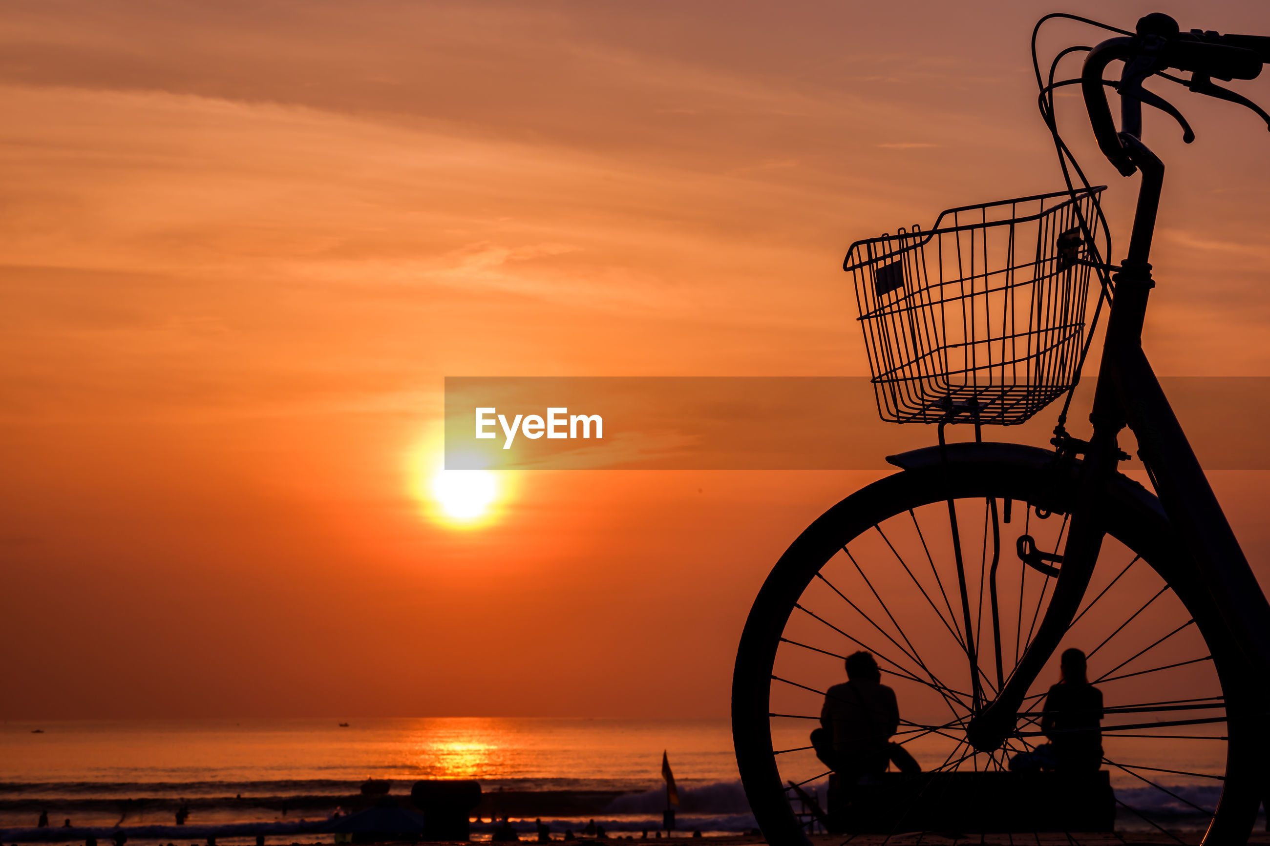 SILHOUETTE OF BICYCLE BY SEA AGAINST SKY DURING SUNSET