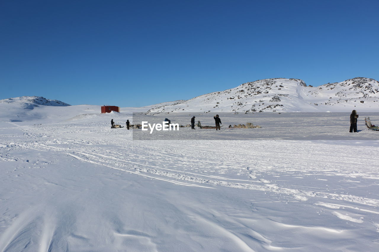 Scenic view of snowy landscape against clear blue sky