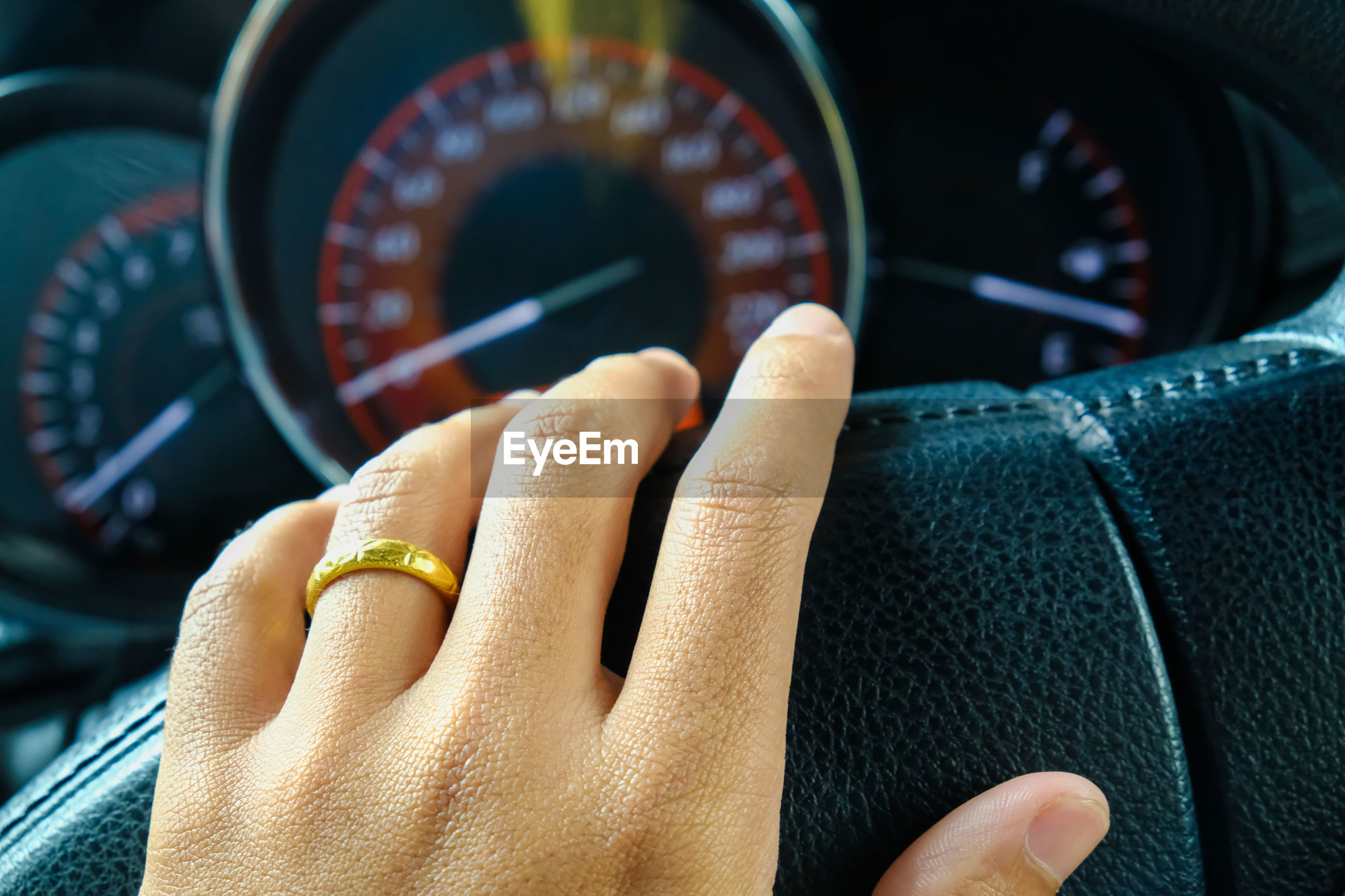 Cropped hand on steering wheel of car