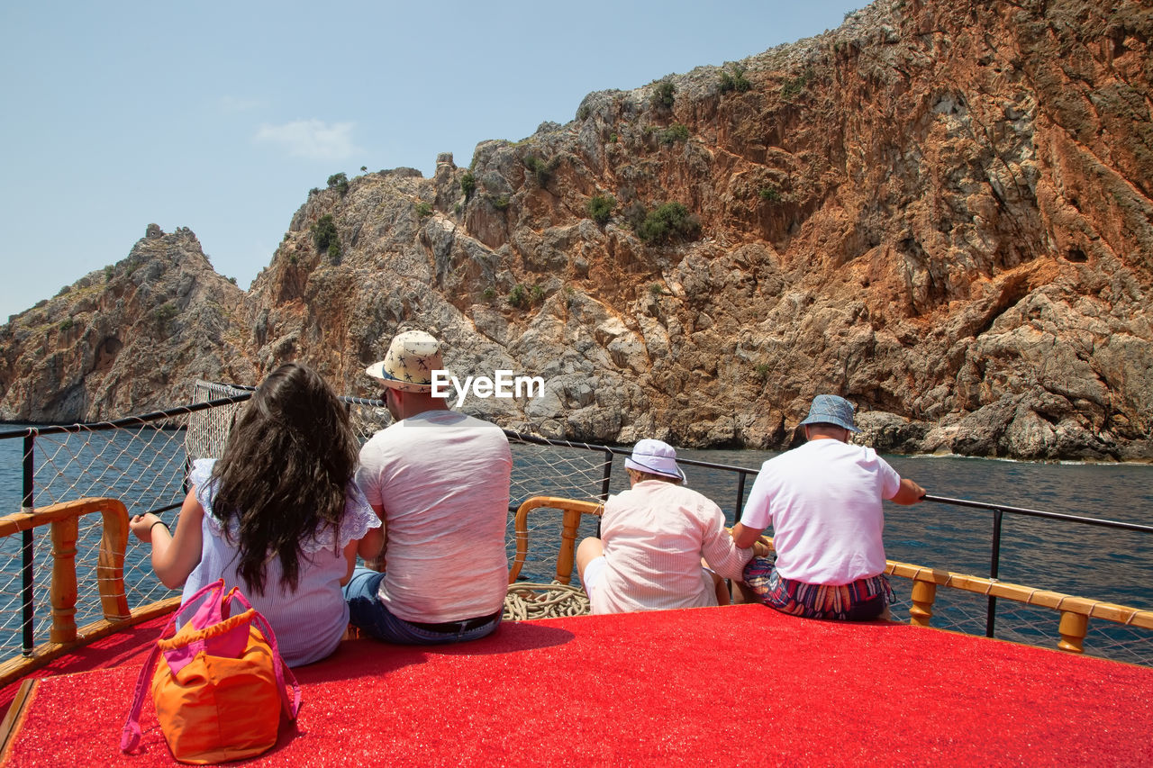 rear view, real people, mountain, men, women, group of people, people, sitting, lifestyles, nature, sky, day, leisure activity, adult, outdoors, rock, red, group, mountain range, water, formation