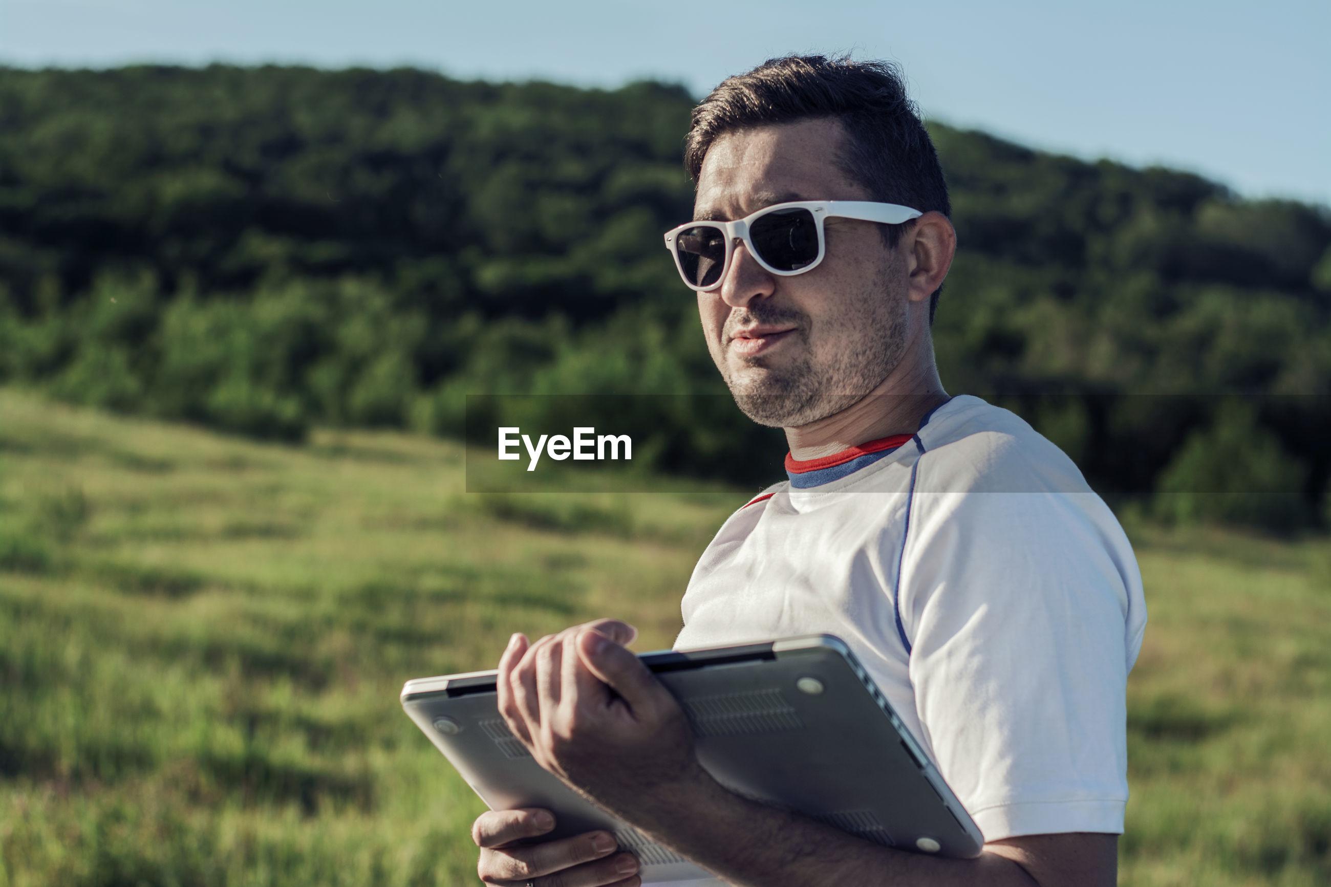Man holding laptop on field