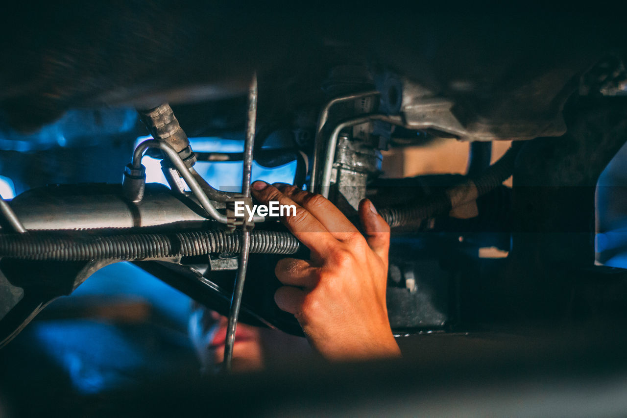 human hand, hand, one person, occupation, holding, real people, working, indoors, human body part, men, selective focus, repairing, technician, auto repair shop, motor vehicle, mechanic, focus on foreground, adult, finger