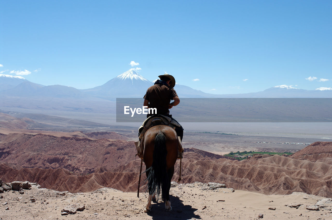 Rear View Of Man Riding Horse At Desert Against Volcano