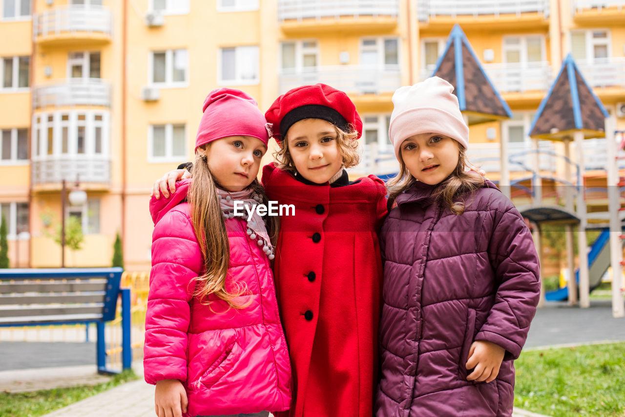 FULL LENGTH PORTRAIT OF HAPPY GIRL STANDING IN PARK