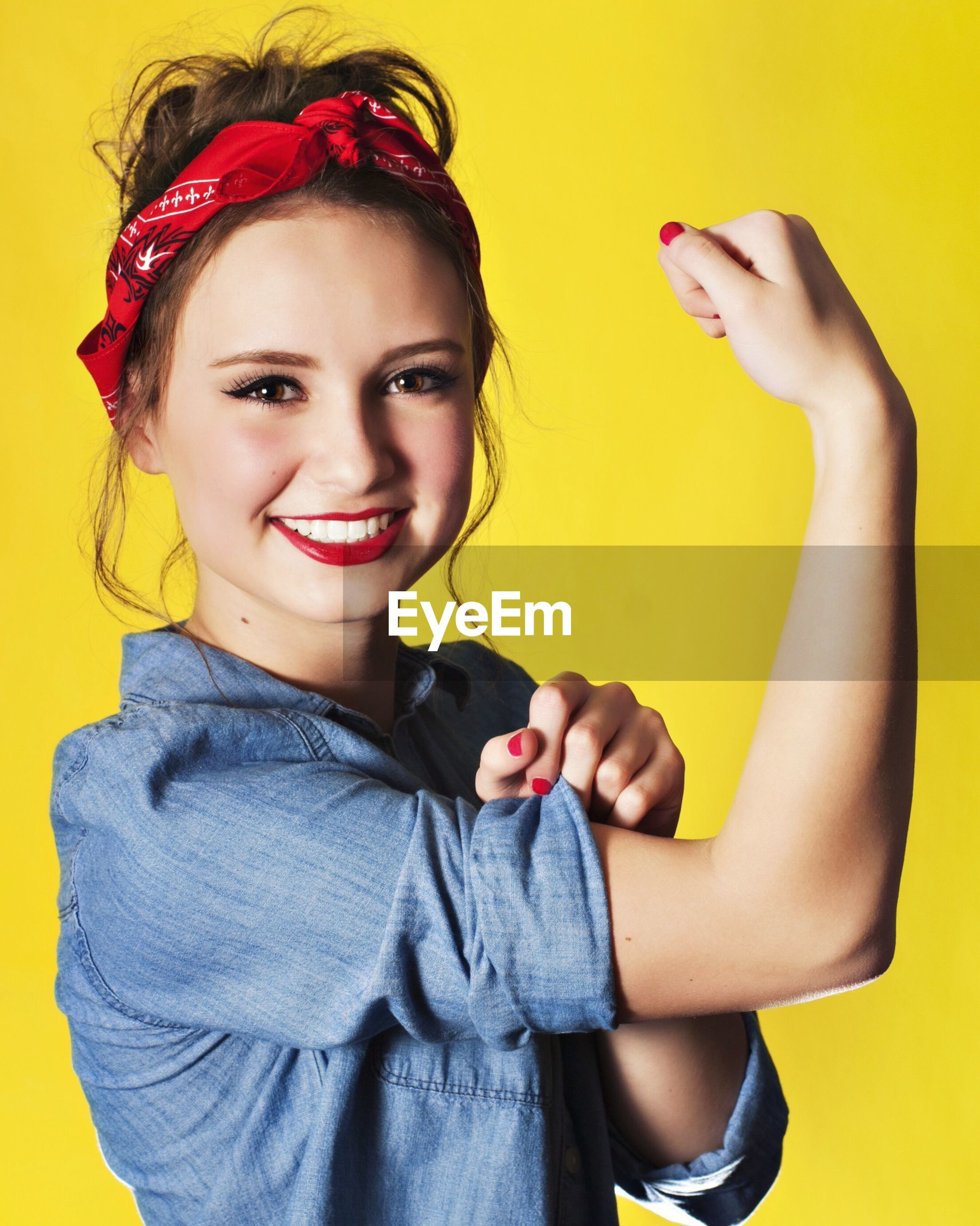 Portrait of smiling teenage girl flexing muscle against yellow background