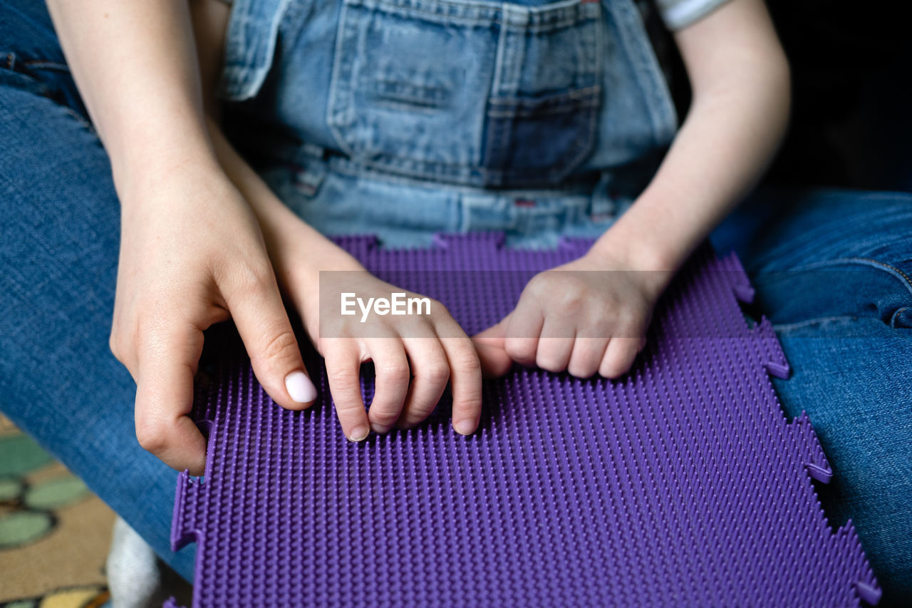MIDSECTION OF WOMAN WITH HANDS ON PURPLE