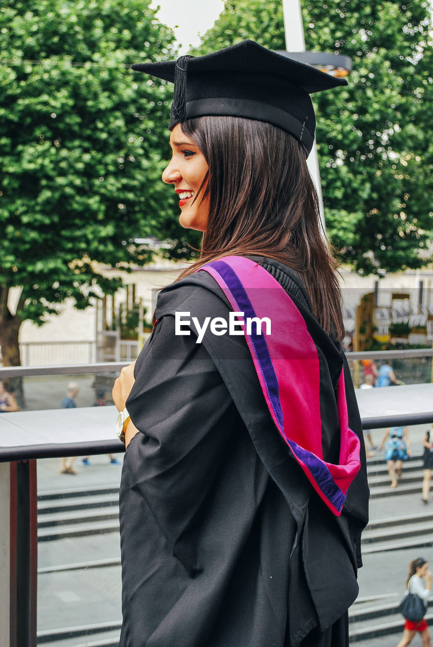 Smiling Young Woman Wearing Mortarboard Against Trees