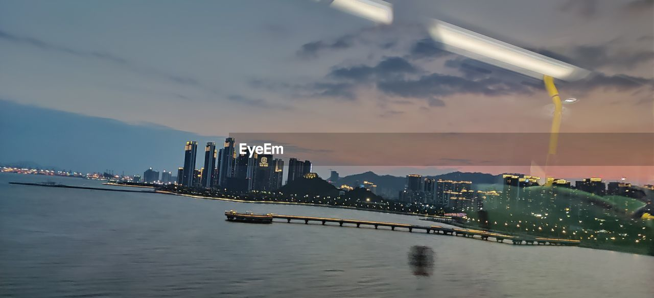 water, architecture, building exterior, built structure, sky, city, no people, cloud - sky, waterfront, illuminated, cityscape, nature, building, urban skyline, office building exterior, skyscraper, landscape, motion, outdoors, financial district