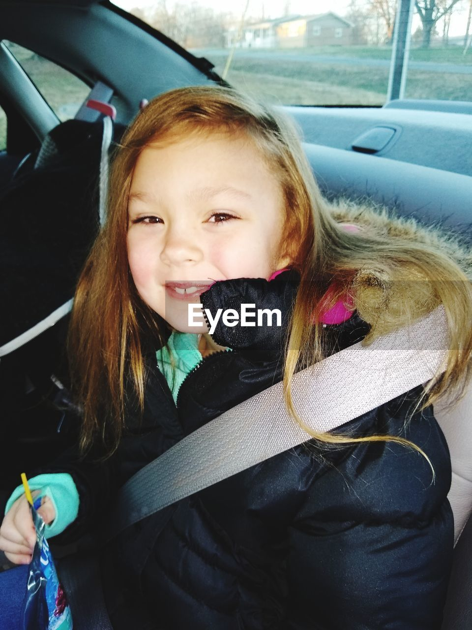 vehicle interior, mode of transportation, transportation, car, motor vehicle, portrait, real people, car interior, land vehicle, childhood, child, females, one person, looking at camera, clothing, seat belt, smiling, women, cute, innocence, warm clothing, road trip, hairstyle