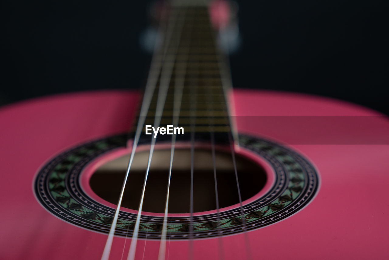 musical instrument, music, string instrument, musical equipment, arts culture and entertainment, guitar, indoors, musical instrument string, string, close-up, studio shot, acoustic guitar, still life, selective focus, no people, black background, fretboard, focus on foreground, wood - material, single object