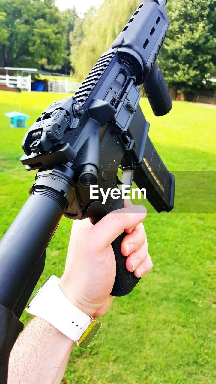 human hand, field, grass, outdoors, human body part, leisure activity, real people, day, camera - photographic equipment, one person, technology, weapon, nature, close-up