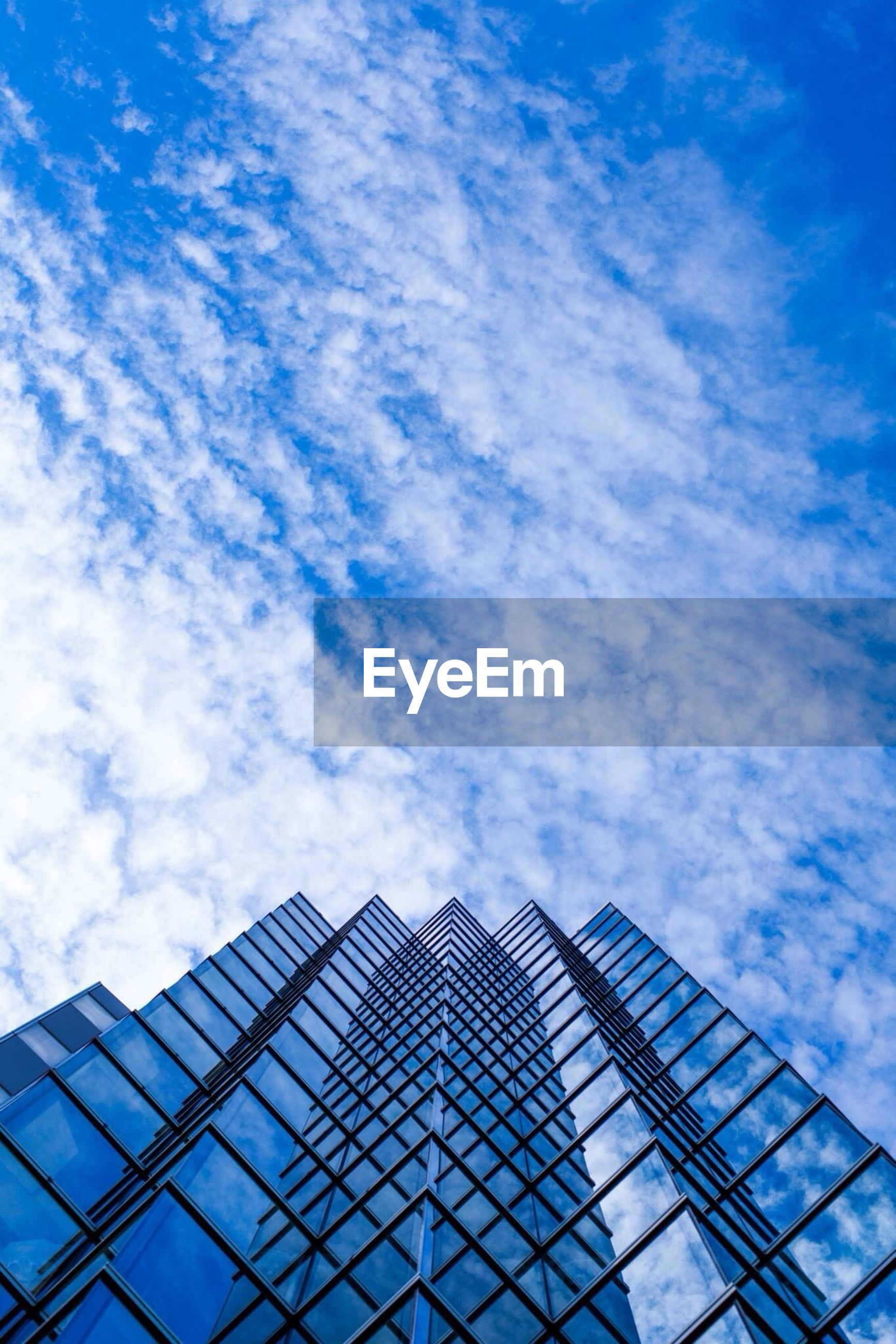 low angle view, sky, blue, built structure, architecture, cloud - sky, modern, building exterior, office building, reflection, cloud, glass - material, pattern, tall - high, day, cloudy, city, building, outdoors, skyscraper