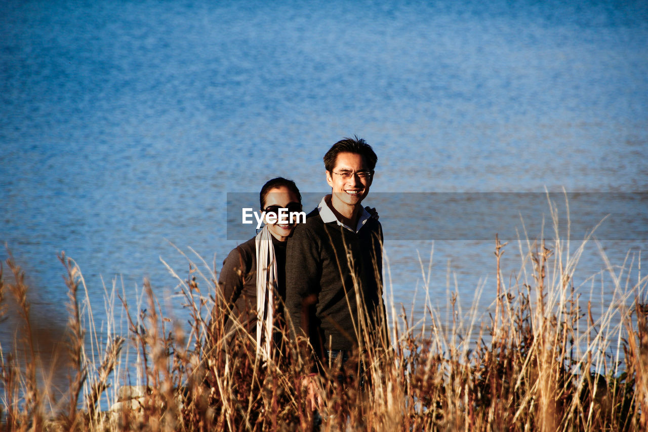 Portrait Of Couple Standing On Field Against Sea