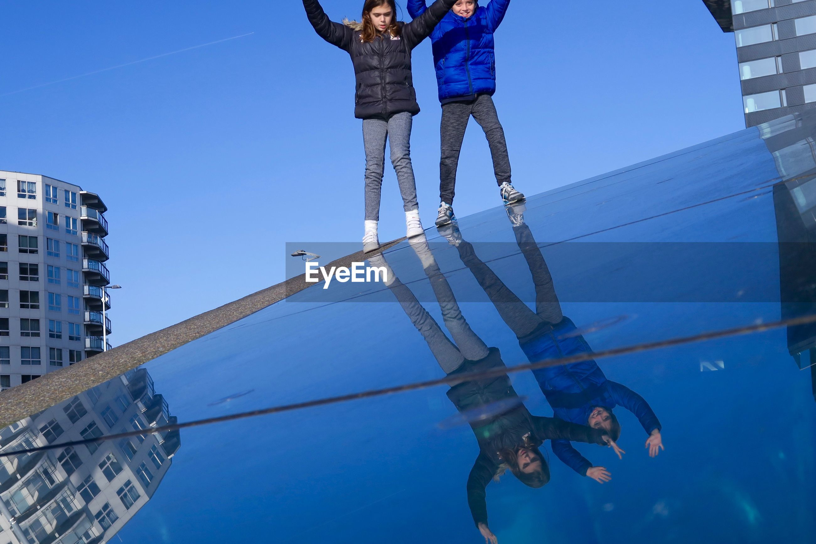 Low angle view of friends standing on steep glass floor against sky