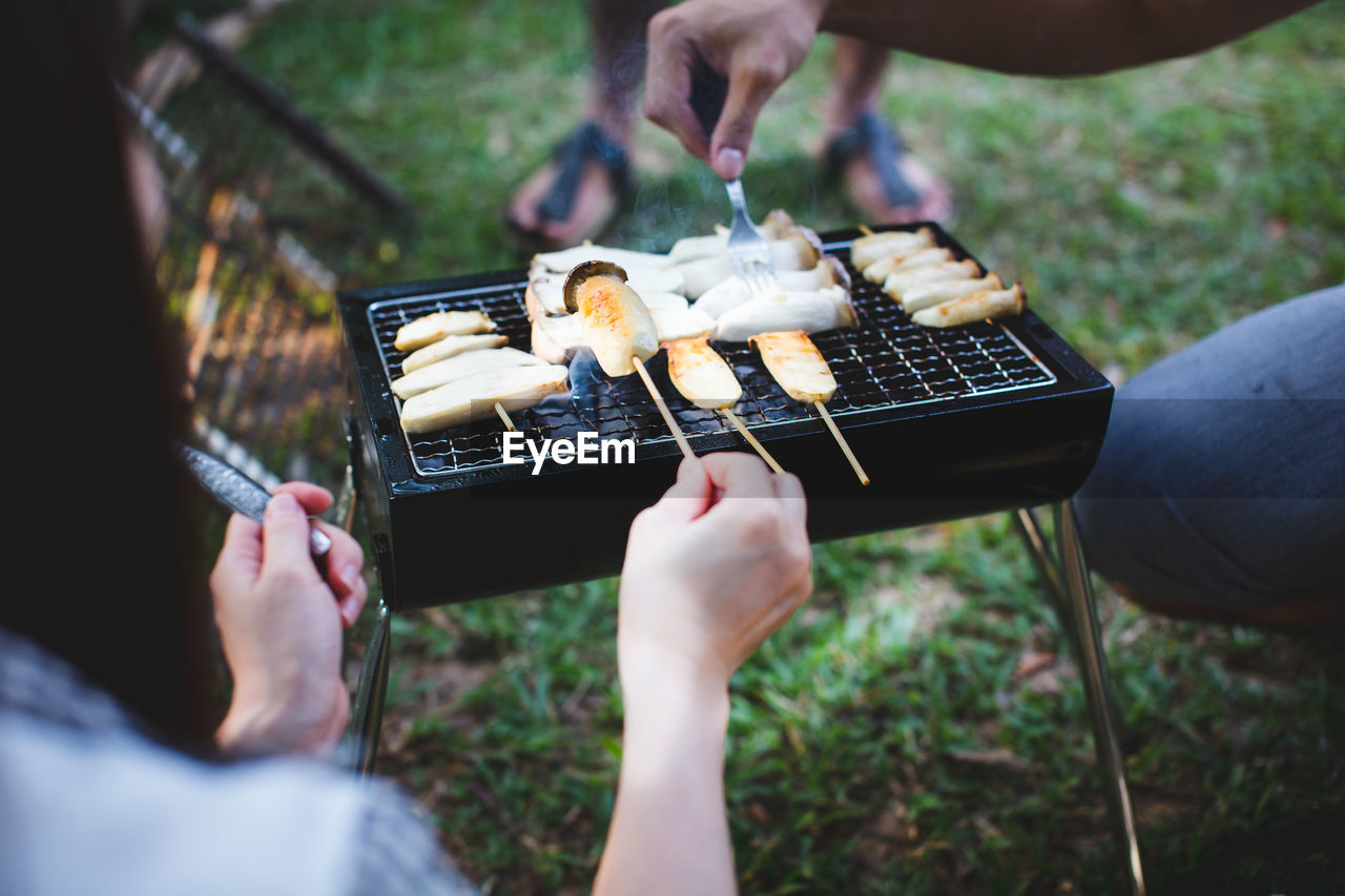 Close-Up Of People Preparing Food On Barbecue Grill In Yard