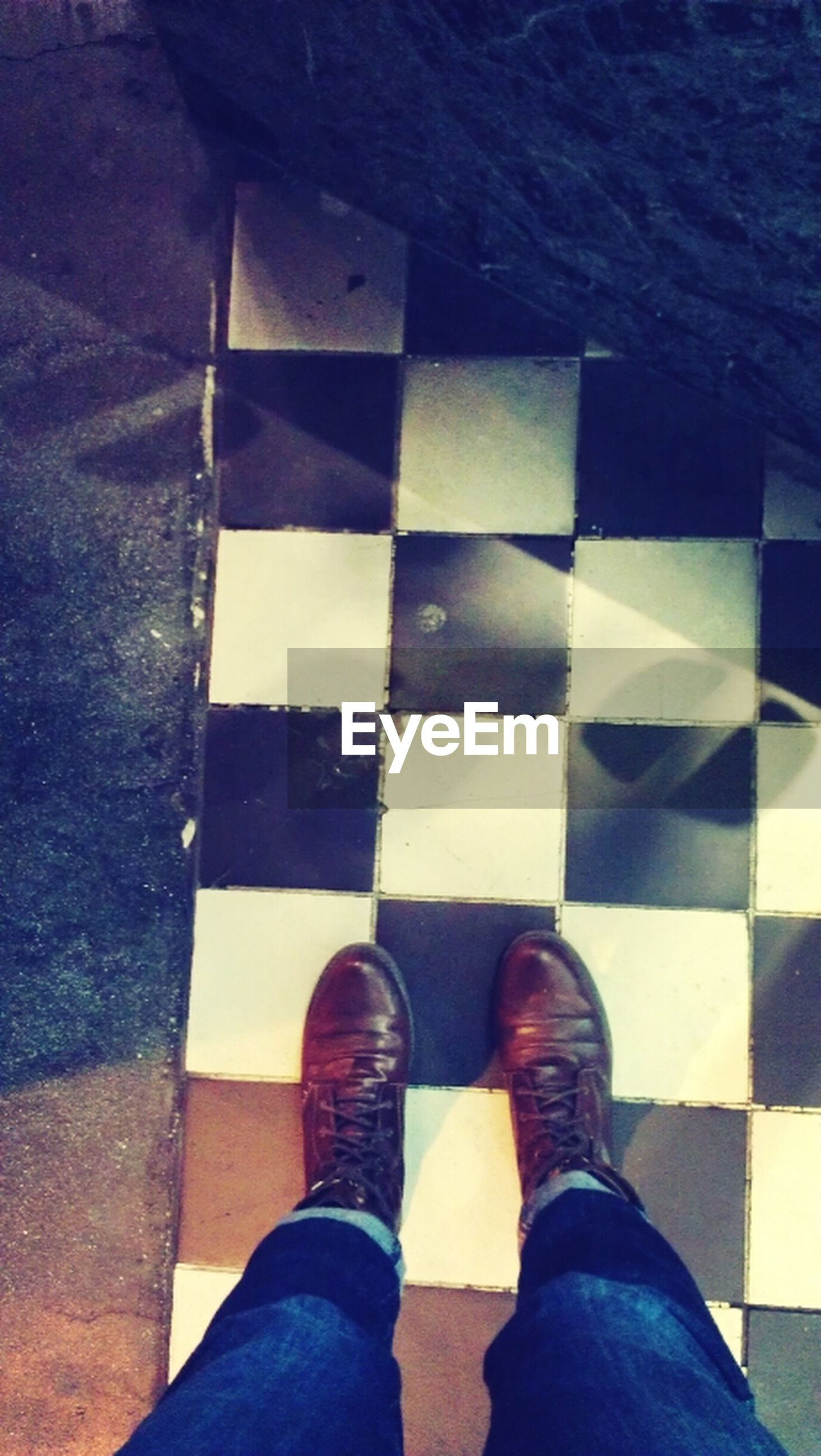 low section, person, shoe, personal perspective, human foot, standing, footwear, high angle view, jeans, lifestyles, men, unrecognizable person, directly above, indoors, tiled floor, flooring, blue
