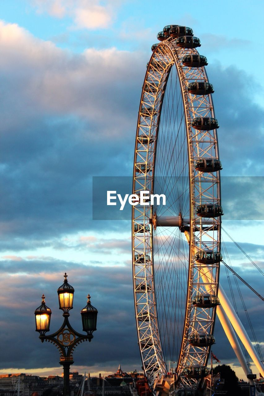 LOW ANGLE VIEW OF FERRIS WHEEL AND FERRIS WHEEL AGAINST CLOUDY SKY