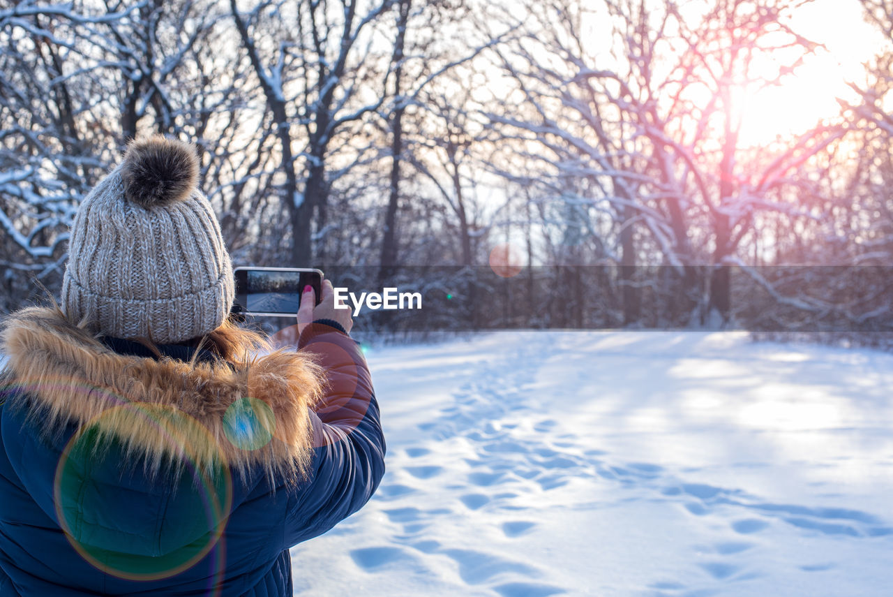 winter, snow, warm clothing, cold temperature, tree, real people, clothing, one person, rear view, bare tree, nature, leisure activity, lifestyles, plant, women, beauty in nature, technology, adult, day, outdoors, hairstyle