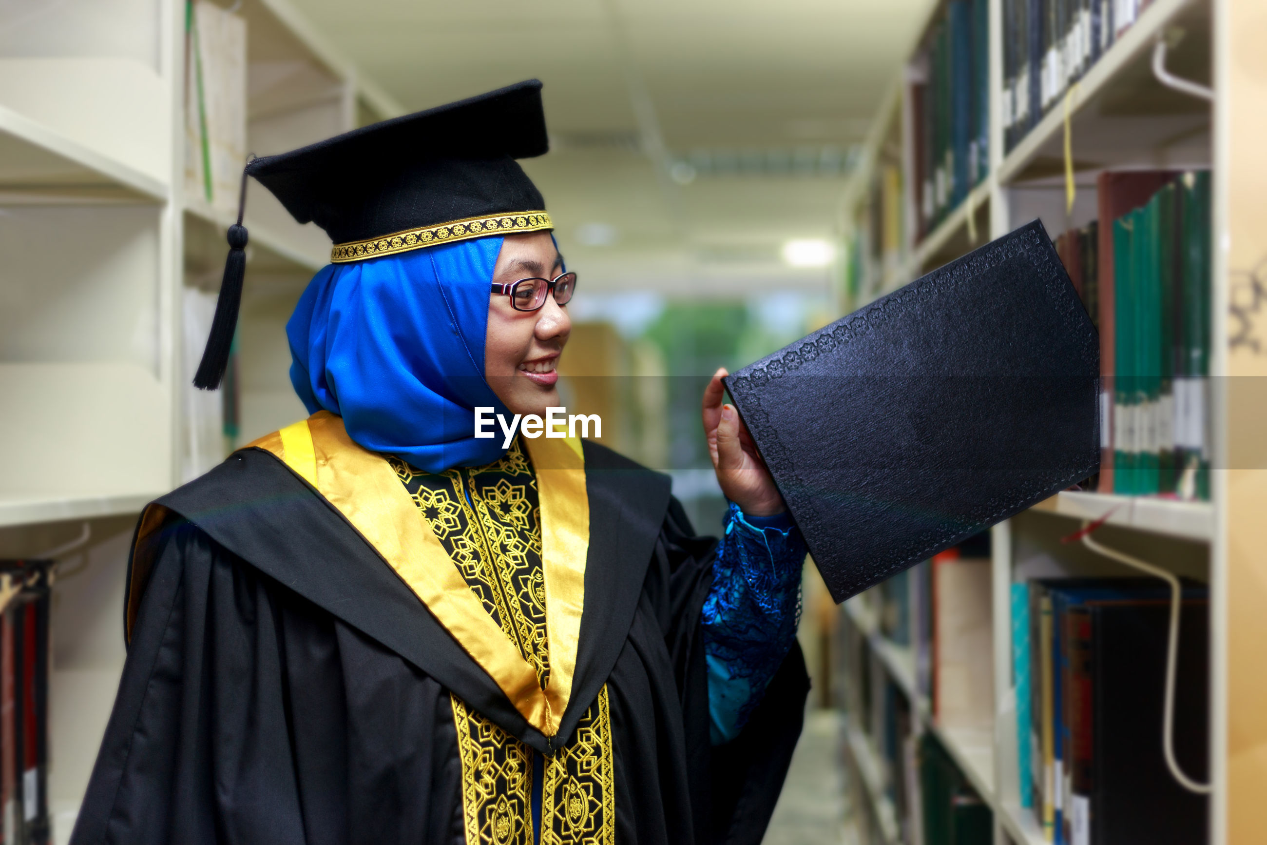 Young woman wearing graduation gown putting book on shelf in library