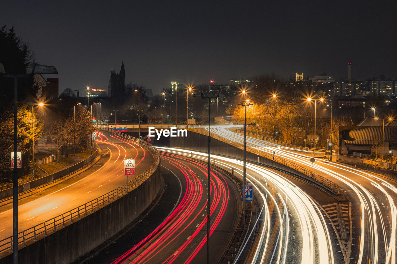 speed, light trail, long exposure, motion, illuminated, night, blurred motion, high street, transportation, traffic, high angle view, no people, road, urban scene, outdoors, architecture