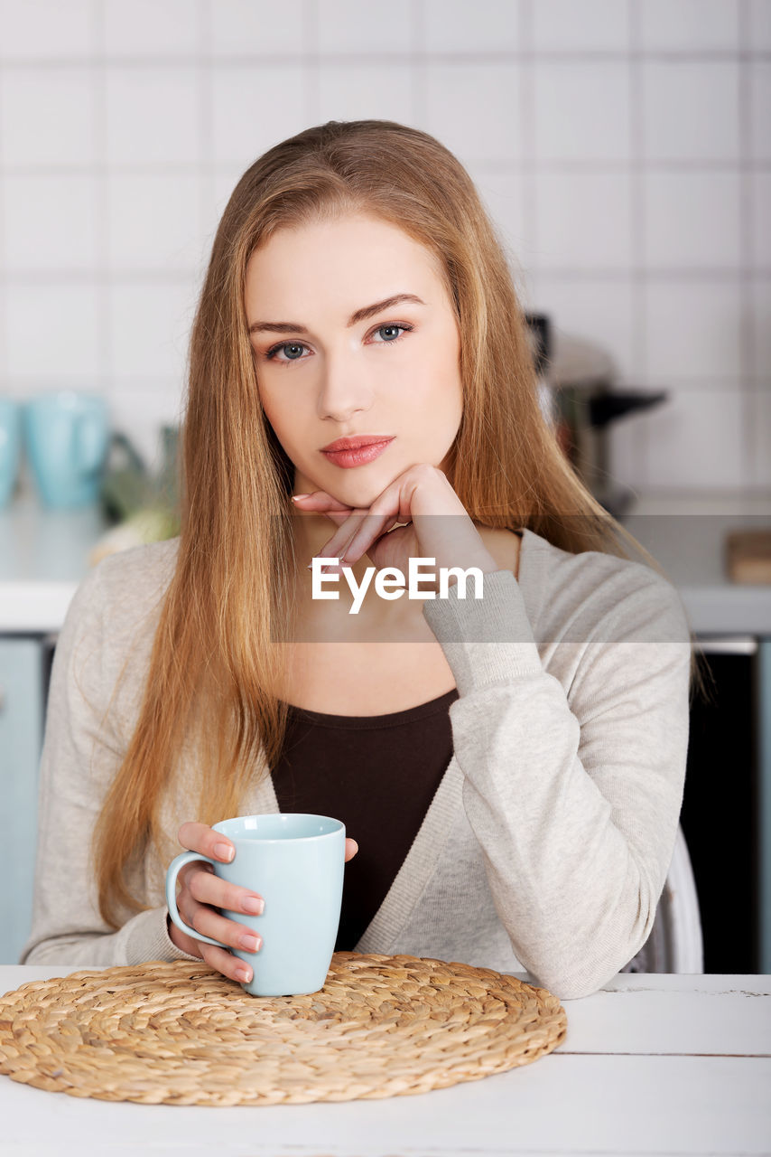 Portrait Of Young Woman Holding Coffee Cup On Table At Home