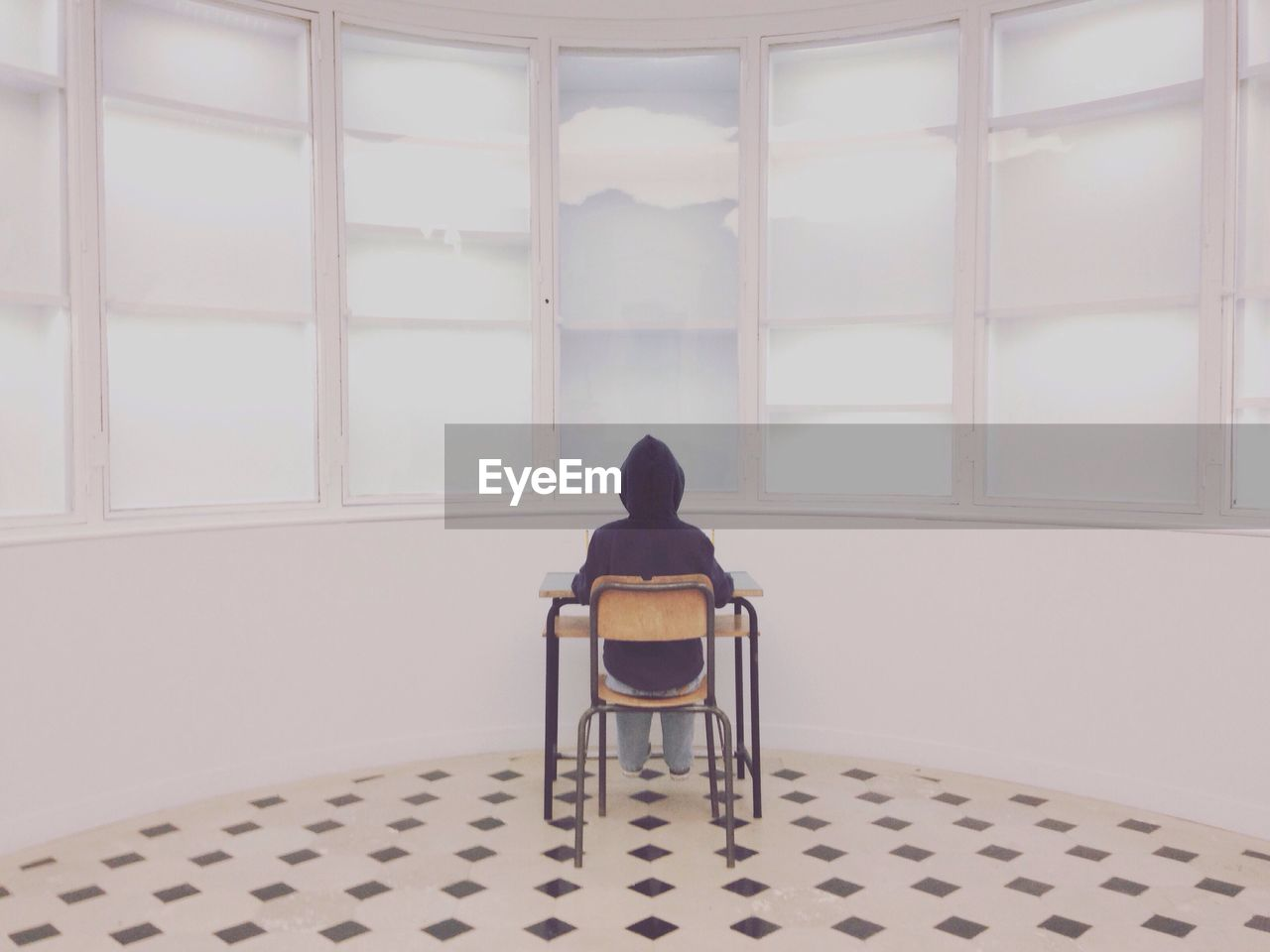 Rear View Of Person Sitting At School Desk